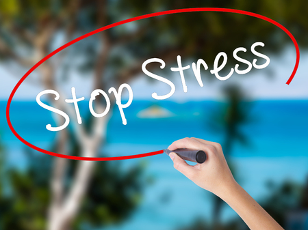 concern: Woman Hand Writing Stop Stress with black marker on visual screen. Isolated on nature. Business concept. Stock Photo