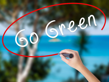 Woman Hand Writing Go Green with black marker on visual screen. Isolated on nature. Business concept. Stock Photo Foto de archivo