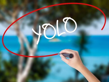 Woman Hand Writing YOLO (You Only Live Once) with black marker on visual screen. Isolated on nature. Business concept. Stock Photo Stock Photo