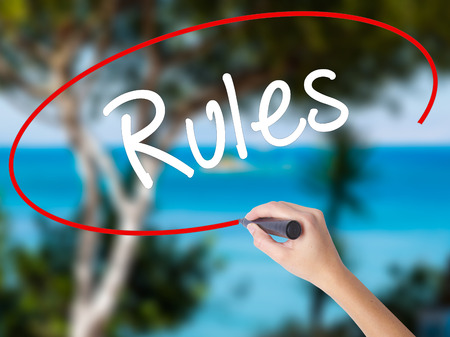Woman Hand Writing Rules with black marker on visual screen. Isolated on nature. Business concept. Stock Photo