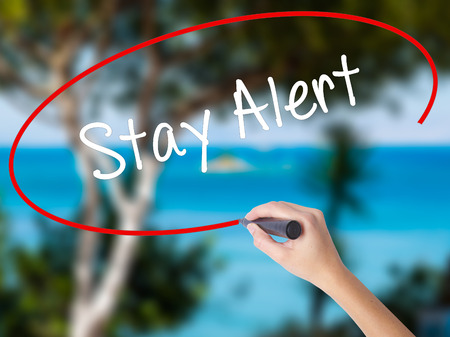 Woman Hand Writing Stay Alert with black marker on visual screen. Isolated on nature. Business concept. Stock Photo