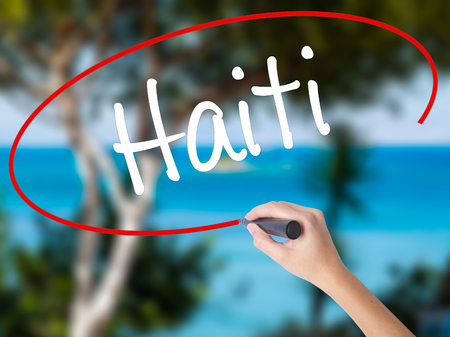 haitian: Woman Hand Writing Haiti with black marker on visual screen. Isolated on nature. Business concept. Stock Photo