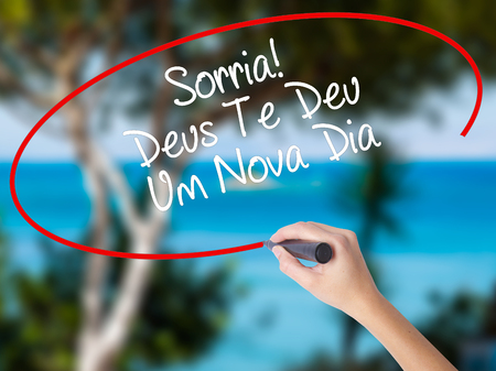 te: Woman Hand Writing Sorria! Deus Te Deu Um Novo Dia (Smile! God Gives You Another Day in Portuguese) with black marker on visual screen. Isolated on nature. Business,  internet concept. Stock Photo