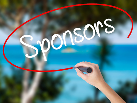 Woman Hand Writing Sponsors with black marker on visual screen. Isolated on nature. Business concept. Stock Photo