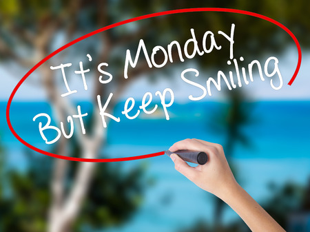 Woman Hand Writing Its Monday But Keep Smiling with black marker on visual screen. Isolated on nature. Business concept. Stock Photo
