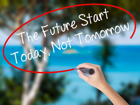 Woman Hand Writing The Future Start Today, Not Tomorrow with black marker on visual screen. Isolated on nature. Business concept. Stock Photo