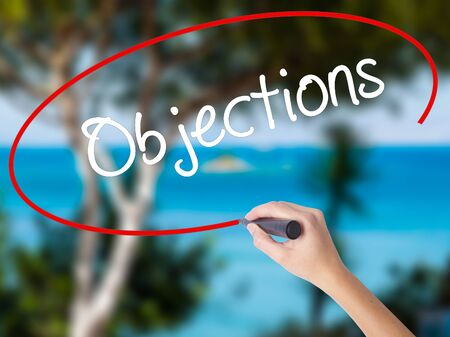 objections: Woman Hand Writing Objections  with black marker on visual screen. Isolated on nature. Business concept. Stock Photo