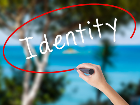 Woman Hand Writing Identity with black marker on visual screen. Isolated on nature. Business concept. Stock Photo
