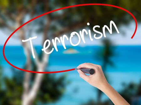 Woman Hand Writing Terrorism with black marker on visual screen. Isolated on nature. Business concept.