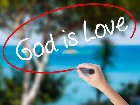 Woman Hand Writing God is Love with black marker on visual screen. Isolated on nature. Business concept. Stock Photo