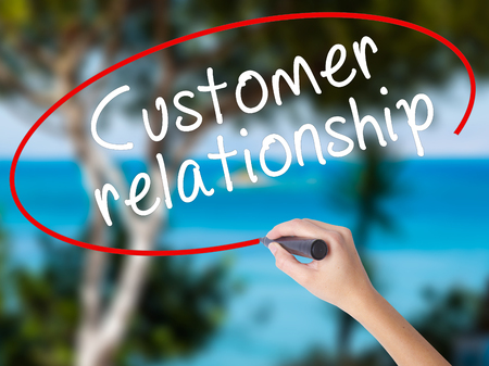Woman Hand Writing Customer relationship with black marker on visual screen. Isolated on nature. Business concept. Stock Photo Stock Photo