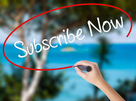 Woman Hand Writing Subscribe Now with black marker on visual screen. Isolated on nature. Business concept. Stock Photo