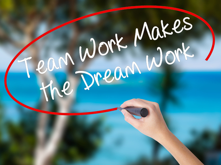 Woman Hand Writing Team Work Makes the Dream Work with black marker on visual screen. Isolated on nature. Business concept. Stock Photo