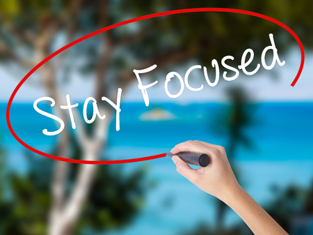 Woman Hand Writing Stay Focused with black marker on visual screen. Isolated on nature. Business,  technology, internet concept. Stock Photo