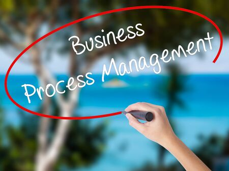 Woman Hand Writing Business Process Management with black marker on visual screen. Isolated on nature. Business concept. Stock Photo