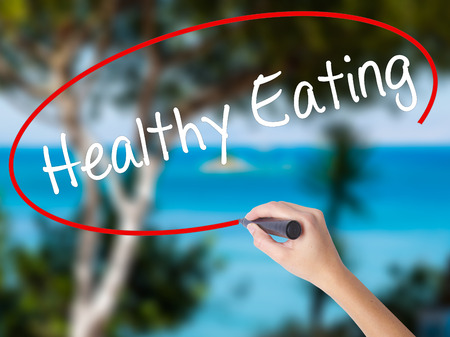 guidepost: Woman Hand Writing Healthy Eating with black marker on visual screen. Isolated on nature. Life, technology, internet concept. Stock Image Stock Photo