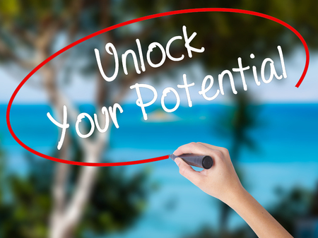 Woman Hand Writing Unlock Your Potential with black marker on visual screen. Isolated on nature. Business concept. Stock Photo