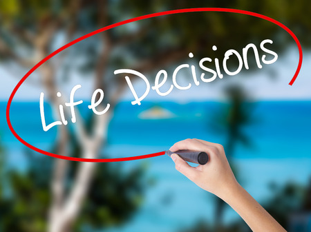Woman Hand Writing Life Decisions with black marker on visual screen. Isolated on nature. Business concept. Stock Photo