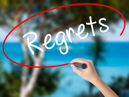 Woman Hand Writing  Regrets with black marker on visual screen. Isolated on nature. Business concept. Stock Photo