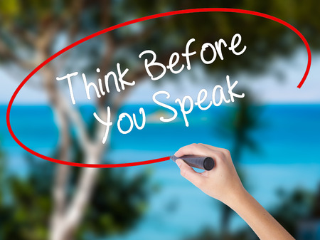 Woman Hand Writing Think Before You Speak with black marker on visual screen. Isolated on nature. Business concept. Stock Photo