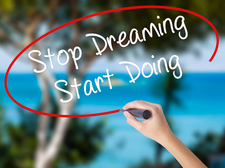 Woman Hand Writing Stop Dreaming Start Doing  with black marker on visual screen. Isolated on nature. Business concept. Stock Photo