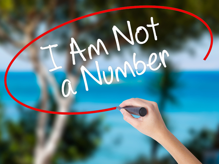 Woman Hand Writing I Am Not a Number with black marker on visual screen. Isolated on nature. Business concept. Stock Photo Stock Photo