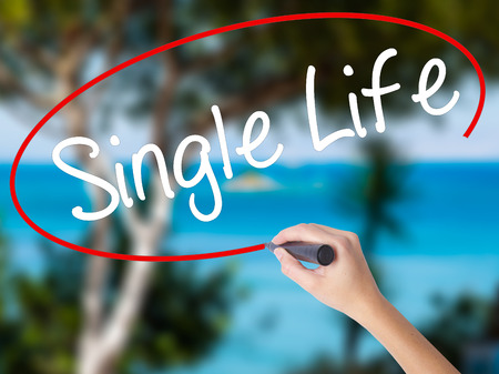 Woman Hand Writing Single Life with black marker on visual screen. Isolated on nature. Business concept. Stock Photo Stock Photo