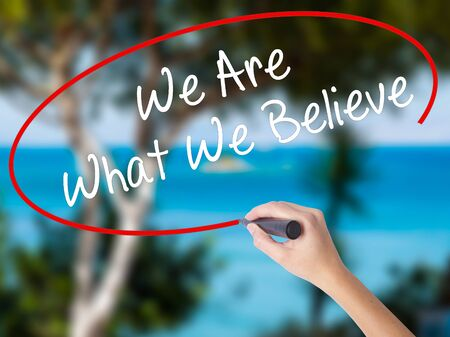 Woman Hand Writing We Are What We Believe with black marker on visual screen. Isolated on nature. Business concept. Stock Photo