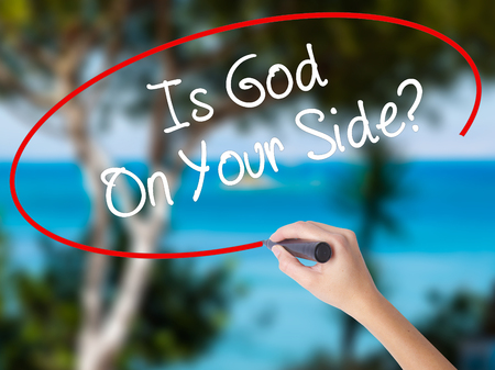 Woman Hand Writing Is God On Your Side? with marker on visual screen. Isolated on nature. Business concept. Stock Photo Stock Photo