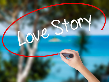 Woman Hand Writing Love Story with black marker on visual screen. Isolated on nature. Business concept. Stock Photo