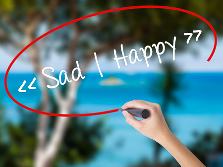 Woman Hand Writing Sad - Happy with black marker on visual screen. Isolated on nature. Business concept. Stock Photo Stock Photo
