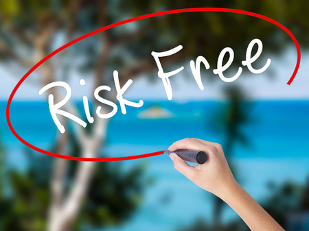 Woman Hand Writing Risk Free with black marker on visual screen. Isolated on nature. Business concept. Stock Photo