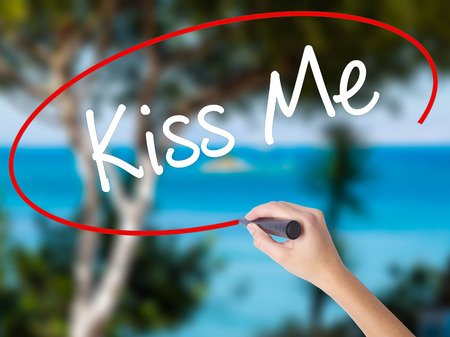 Woman Hand Writing Kiss Me with black marker on visual screen. Isolated on nature. Business concept. Stock Photo Stock Photo