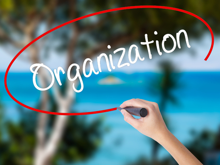 Woman Hand Writing Organization  with black marker on visual screen. Isolated on nature. Business concept. Stock Photo Stock Photo