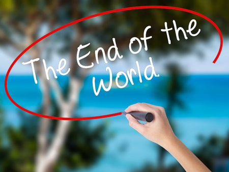 Woman Hand Writing The End of the World with black marker on visual screen. Isolated on nature. Business concept. Stock Photo Stock Photo