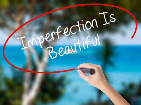 perfectionist: Woman Hand Writing Imperfection Is Beautiful with black marker on visual screen. Isolated on nature. Business concept. Stock Photo Stock Photo