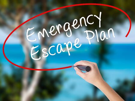 Woman Hand Writing Emergency Escape Plan with black marker on visual screen. Isolated on nature. Business concept. Stock Photo