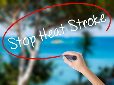 Woman Hand Writing Stop Heat Stroke with black marker on visual screen. Isolated on nature. Business concept. Stock Photo