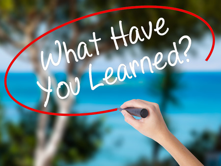 Woman Hand Writing What Have You Learned? with black marker on visual screen. Isolated on nature. Business concept. Stock Photo