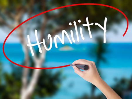 humildad: Woman Hand Writing Humility  with black marker on visual screen. Isolated on nature. Business concept. Stock Photo
