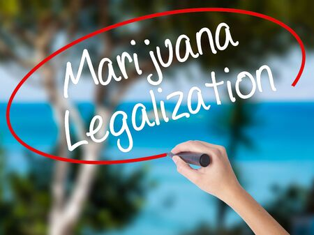Woman Hand Writing Marijuana Legalization with black marker on visual screen. Isolated on nature. Live, technology, internet concept. Stock Photo