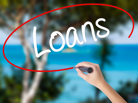 Woman Hand Writing Loans  with black marker on visual screen. Isolated on nature. Business concept. Stock Photo