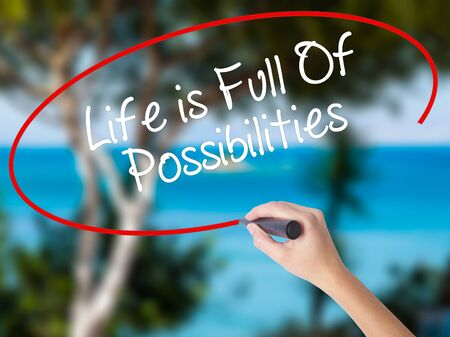 Woman Hand Writing Life is Full Of Possibilities with black marker on visual screen. Isolated on nature. Business concept. Stock Photo