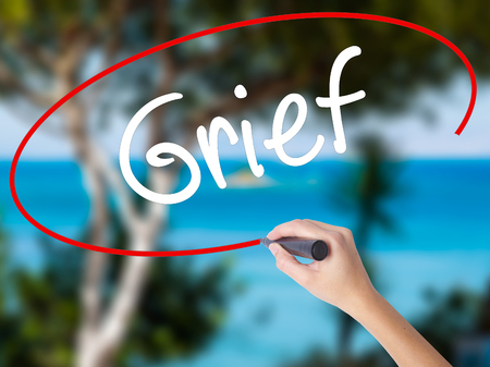 Woman Hand Writing Grief with black marker on visual screen. Isolated on nature. Business concept. Stock Photo