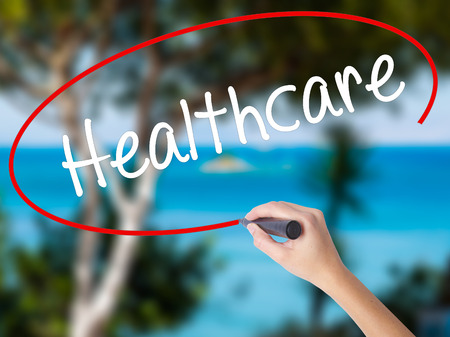 Woman Hand Writing Healthcare with black marker on visual screen. Isolated on nature. Business concept. Stock Photo
