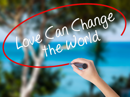 Woman Hand Writing Love Can Change the World with black marker on visual screen. Isolated on nature. Business concept. Stock Photo