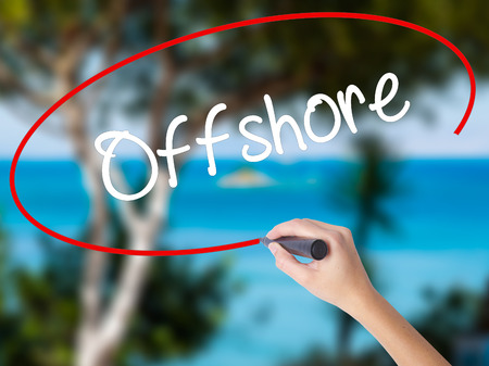 Woman Hand Writing Offshore with black marker on visual screen. Isolated on nature. Business concept. Stock Photo Stock Photo