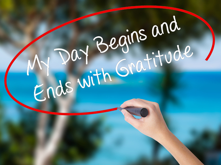 Woman Hand Writing My Day Begins and Ends with Gratitude with black marker on visual screen. Isolated on nature. Business concept. Stock Photo