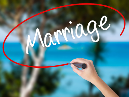 Woman Hand Writing Marriage with black marker on visual screen. Isolated on nature. Business concept. Stock Photo