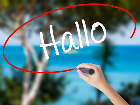 hallo: Woman Hand Writing Hallo  (Hello in German) with black marker on visual screen. Isolated on nature. Business concept. Stock Photo